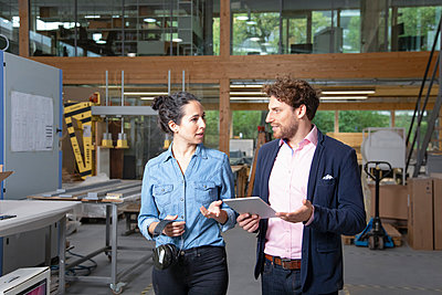 Businessman and businesswoman discussing strategy in factory - p300m2265999 by Florian Küttler