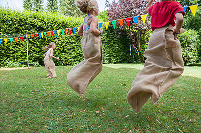 Children having a sack race in garden on a birthday party - p300m838589f by Nico Hermann
