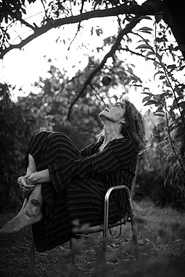 Woman sitting beneath apple tree - p310m2263857 by Astrid Doerenbruch