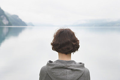 Woman staring at a lake in Switzerland - p4641124 by Elektrons 08