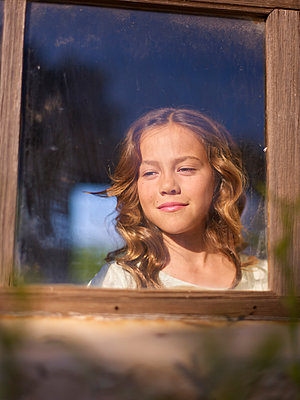 Girl looking out of window - p885m2177924 by Oliver Brenneisen