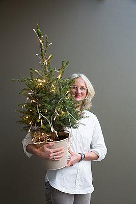 Frau hält kleinen, geschmückten Weihnachtsbaum im Arm. - p948m2014772 von Sibylle Pietrek