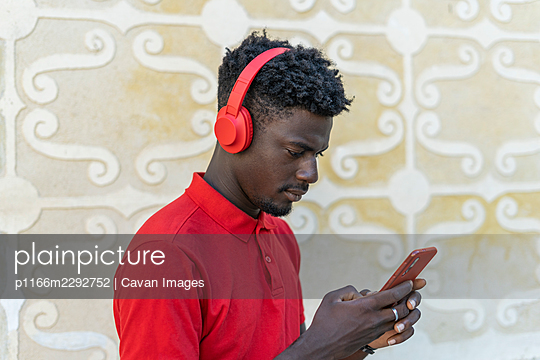 African male using smart phone and listening music in red headphones - p1166m2292752 by Cavan Images
