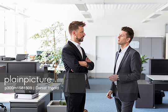 Two businessmen standing in office, discussing solutions - p300m1581509 von Daniel Ingold