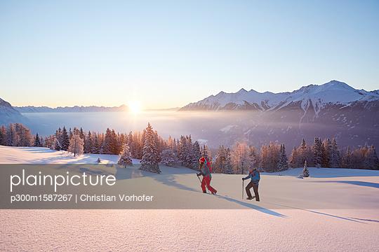 Austria, Tyrol, snowshoe hikers at sunrise - p300m1587267 von Christian Vorhofer