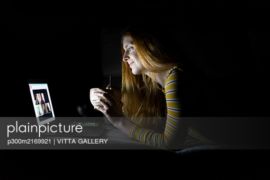 Young woman having a laptop video conference on the couch at home while having dinner - p300m2169921 by VITTA GALLERY