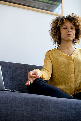 Young woman sitting on couch at home next to laptop meditating - p300m1536233 by harry + lidy