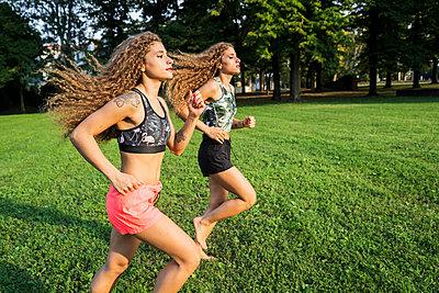 Twin sisters jogging barefoot in a park - p300m2060010 by Giorgio Fochesato