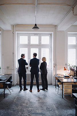 Business people standing at the window in office - p300m2154900 by Gustafsson