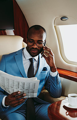 Young businessman reading newspaper while talking on smart phone in airplane - p300m2257047 by OneInchPunch