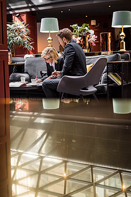 Businesswoman signing agreement by male partner sitting in hotel reception - p426m1442724 by Maskot