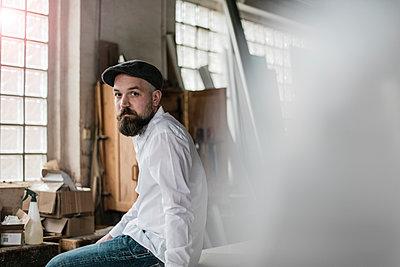 Besorgter Tischler sitzt in seiner Werkstatt - p586m1496229 von Kniel Synnatzschke