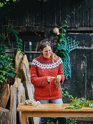 Woman tying bunch of herbs - p962m2175378 by Robert Schlossnickel