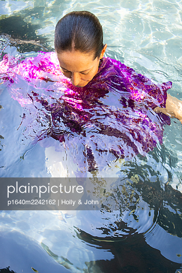 Woman in purple dress swims in the swimming pool - p1640m2242162 by Holly & John