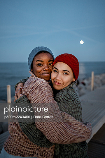 Smiling friends wearing knit hat embracing each other while standing against sky - p300m2243466 by Rafa Cortés