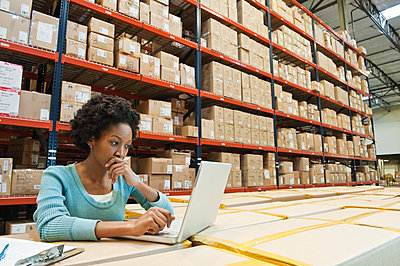 African American female warehouse worker working on inventory on a lap top computer in a large distribution warehouse of products stored in cardboard boxes and on large racks. - p1100m1575503 by Mint Images