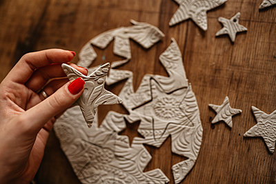 hand of young woman creating clay stars as Christmas ornaments - p1166m2235304 by Cavan Images