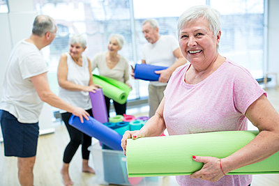 Happy senior woman holding yoga mat after class - p300m2207056 by Fotoagentur WESTEND61