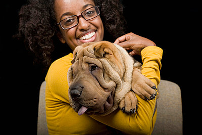 A young woman with her Shar-Pei, studio shot - p3018220f by Winnie Au