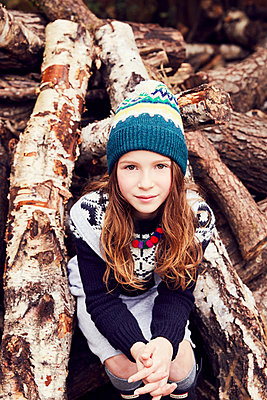 Portrait of young girl, sitting on log pile - p429m1408111 by Emma Kim