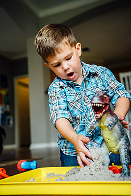 Caucasian boy playing with toy dinosaur - p555m1304491 by Inti St Clair