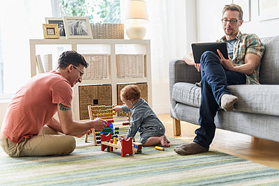 Caucasian gay fathers and baby relaxing in living room - p555m1412815 by JGI/Tom Grill
