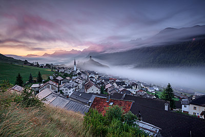 Pink clouds and mist on the village of Ardez at dawn, district of Inn, Lower Engadine, Canton of Graubunden, Switzerland, Europe - p871m1499877 by Roberto Moiola