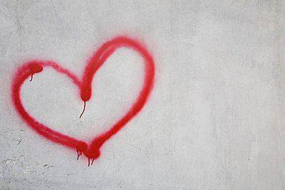 Red heart shape on white wall - p9242479f by Image Source