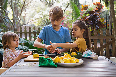 Boy and two young sisters preparing lemon juice for lemonade at garden table - p924m1446978 by Kinzie Riehm