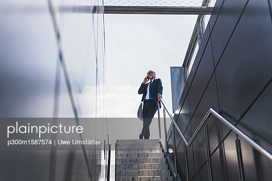 Smiling mature businessman at staircase in the city on cell phone - p300m1587574 von Uwe Umstätter