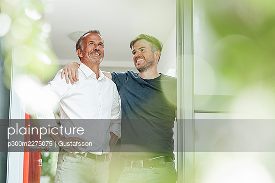 Son with arm around father looking at father while standing at doorway - p300m2275075 by Gustafsson