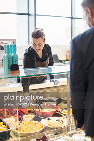 Saleswoman selling organic food to mature man in supermarket - p426m1407382 by Kentaroo Tryman