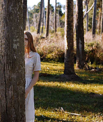 Unrecognizable red-haired young woman standing behind the tree in a sunny forest   - p1694m2291640 by Oksana Wagner