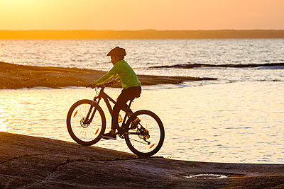 Boy cycling on beach at sunset - p312m1557141 by Mikael Svensson