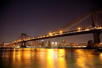 Bridge and city skyline lit up at night - p429m1450608 by Seb Oliver