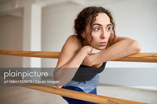Thoughtful woman looking away while leaning on barres at dance studio - p1166m1555670 by Cavan Images
