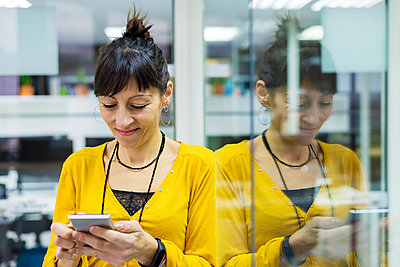 Businesswoman using mobile phone while leaning on glass door at office - p1166m2094797 by Cavan Images