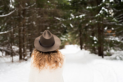 Back view of young woman wearing hat and knit pullover in winter forest - p300m1499323 by HalfPoint