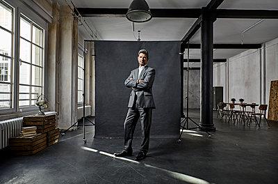 Portrait of mature businessman in front of black backdrop in loft - p300m1581729 von Philipp Dimitri