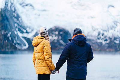 Tourist couple enjoying the view at Hamnoy, Lofoten, Norway - p300m2166493 by Daniel González