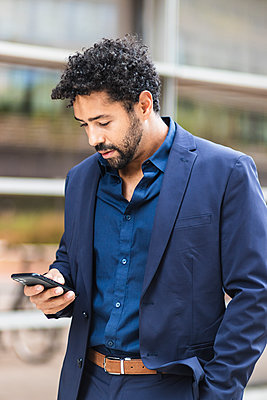 Entrepreneur using mobile phone while standing in city - p300m2227155 by NOVELLIMAGE
