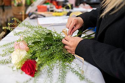 Florist tying bouquet at flower shop - p300m2242804 by Jose Carlos Ichiro
