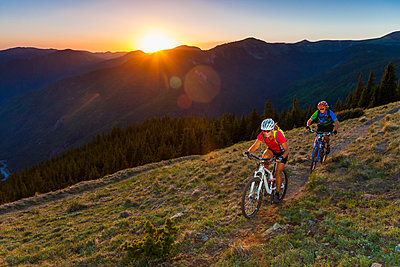 Caucasian couple mountain biking on trail - p555m1491630 by Michael DeYoung
