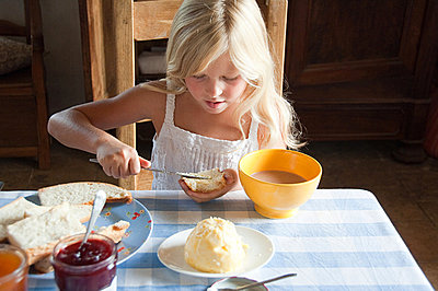 Girls spreading butter on bread - p9244702f by Image Source
