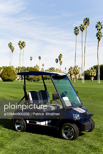 A golf cart parked on a golf course, Palm Springs, California - p1094m900203 by Patrick Strattner