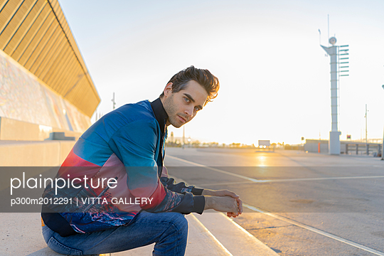 Man sitting on stairs in the city at sunrise - p300m2012291 von VITTA GALLERY
