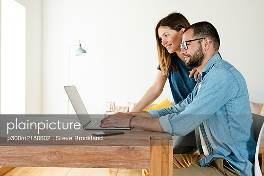 Smiling couple working at laptop from home in home office in modern living room - p300m2180602 by Steve Brookland