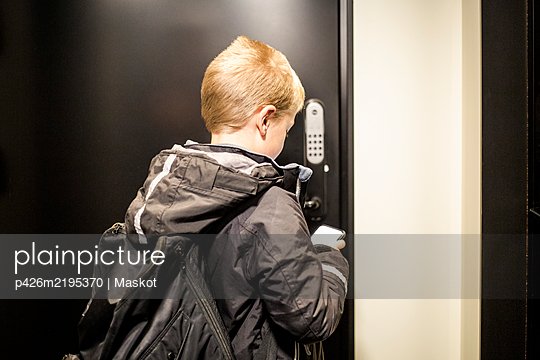 Rear view of boy using app on smart phone to unlock door - p426m2195370 by Maskot