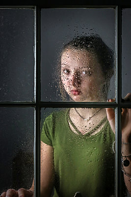 Female teenager behind wet window pane - p1019m2056882 by Stephen Carroll