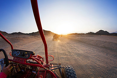 Beach buggies on dessert against clear sky during sunny day - p1166m1037050f by Cavan Images